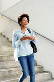 Laughing young african woman walking down the steps. Portrait of young african woman with mobile phone walking down the steps of a building and laughing Stock Photography