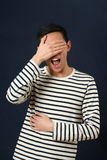 Laughing young Asian man covering his face by palm Royalty Free Stock Images