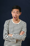 Laughing young Asian man with crossed hands looking at camera Royalty Free Stock Photos