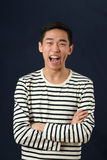 Laughing young Asian man with crossed hands Royalty Free Stock Photos
