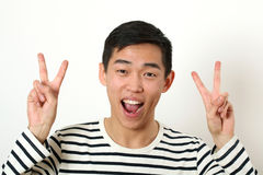 Laughing young Asian man giving two victory signs and looking at Royalty Free Stock Photo