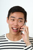 Laughing young Asian man using a smartphone Royalty Free Stock Photos