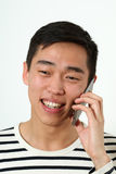 Laughing young Asian man using a smartphone Royalty Free Stock Image