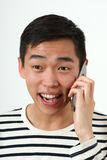 Laughing young Asian man using a smartphone Royalty Free Stock Photography