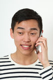 Laughing young Asian man using a smartphone Stock Image