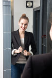 Laughing young beautiful business woman checking her successful working suit Royalty Free Stock Photo