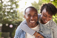 Laughing young black couple piggyback in garden, to camera royalty free stock images