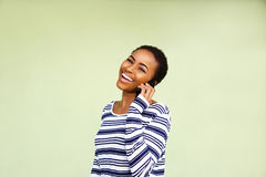 Laughing young black woman with cellphone against green wall Stock Photo