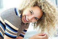 Laughing young black woman leaning over Stock Photo