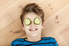 Laughing young boy with cucumber on his eyes Stock Photos