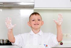 Laughing young boy with floury hands Royalty Free Stock Image