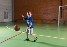 Laughing young boy playing basketball. On an indoor court as he runs along bouncing the ball and grinning at the camera Royalty Free Stock Photography