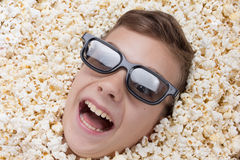 Laughing young boy in stereo glasses looking out of popcorn Royalty Free Stock Images