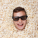 Laughing young boy in stereo glasses looking out of popcorn Royalty Free Stock Photo