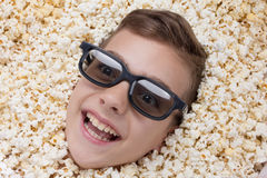 Laughing young boy in stereo glasses looking out of popcorn Stock Images