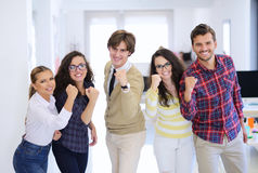 Laughing young business entrepreneurs in trendy clothing celebrating a success. Laughing young business entrepreneurs in informal trendy clothing standing royalty free stock image