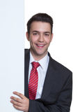 Laughing young businessman behind a white board Stock Images