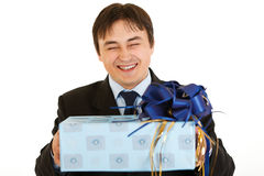 Laughing young businessman holding gift in hands Stock Images
