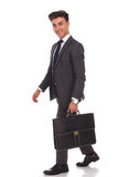 Laughing young businessman is walking with suitcase Royalty Free Stock Image