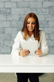 Laughing young businesswoman looking at tablet Stock Photo