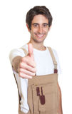 Laughing young carpenter showing thumb Stock Photos