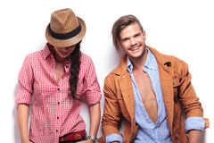 Laughing young casual couple. Women looking down and men at the camera Stock Photography