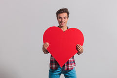 Laughing young casual man holding a big red heart. On grey background Royalty Free Stock Image