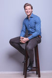 Laughing young casual man sitting Stock Images