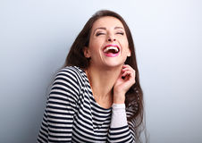 Laughing young casual woman with wide open mouth and closed eyes Stock Photos