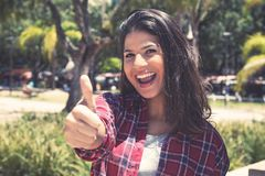 Laughing young caucasian woman showing thumb up stock images