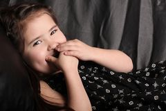Laughing Young Child. Young Child Giggling on the Couch With Hand Over Her Mouth Stock Images