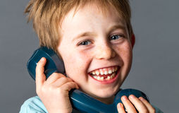 Laughing young child with tooth missing with old telephone Royalty Free Stock Images