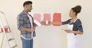 Laughing young couple choosing a paint color stock video