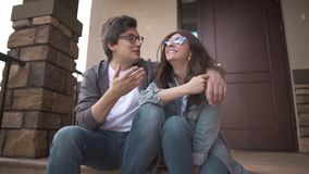 Laughing young couple sitting together on their house porch and talking stock video footage