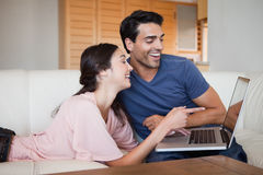Laughing young couple using a laptop Royalty Free Stock Photo