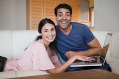 Laughing young couple using a notebook Royalty Free Stock Photography