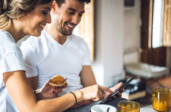 Laughing young couple using tablet at breakfast Royalty Free Stock Photography