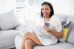 Laughing young dark haired woman in white clothes shopping online with a laptop Stock Photo