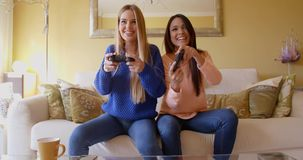 Laughing young female video game players. Front view of happy laughing young women holding game controllers in the living room stock video