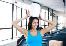 Laughing young fit woman with plastic container on head Royalty Free Stock Image