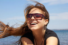 Laughing young girl. In sunglasses near the sea Stock Photos