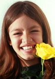 Laughing young girl. Portrait of a happy laughing young girl with long brown hair showing off  lost tooth with a yellow rose Stock Photos