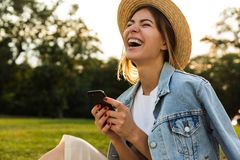 Laughing young girl in summer hat sitting outdoors stock photos