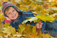 Laughing young girl on the yellow leaves Royalty Free Stock Image