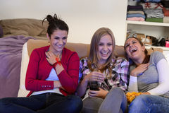 Laughing young girls watching TV together. Sitting on couch Royalty Free Stock Photos