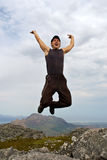 Laughing young hiker jumps high Stock Images
