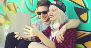 Laughing young hipster couple checking a tablet. Computer as they relax arm in arm in the summer sun in front of colorful graffiti stock video footage