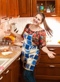 Laughing young housewife in apron on kitchen Stock Images