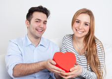Laughing young love couple with a gift Stock Images