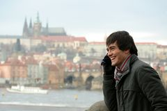 Laughing young man. A happy young man with a cell phone, laughing; the Prague Castle - old city and the Vltava River in the background Royalty Free Stock Photos